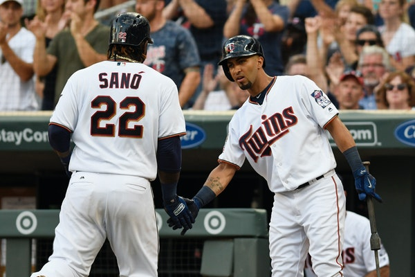 Minnesota Twins' Miguel Sano (22) is congratulated by Eddie Rosario, right, after Sano scored on a double by Robbie Grossman off Detroit Tigers pitche