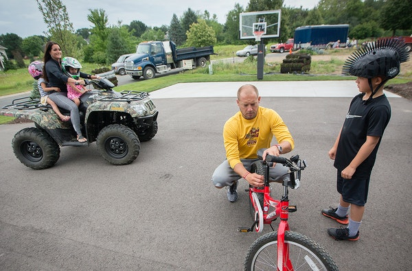 P.J. Fleck worked on his son's Carter's bike as Heather gave the girls a ride on the ATV.