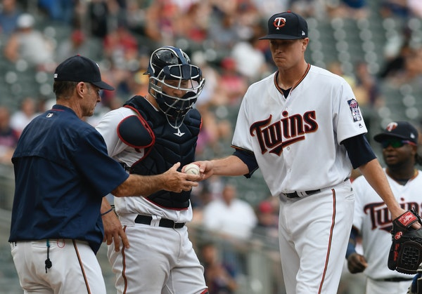 Twins starting pitcher Kyle Gibson, right, hands Twins manager Paul Molitor, left, as he leaves the mound in the fifth inning of a baseball game again