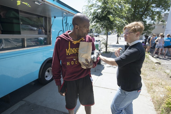 Pastor Margaret Kelly, right, talked with Lucky King who picked up food from Shobi's Table food truck in St. Paul.