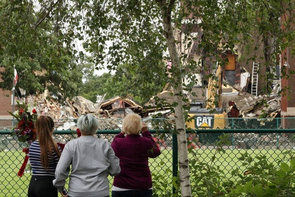 Three women stood near a makeshift memorial outside the fenced-off collapsed building at Minnehaha Academy's Upper School campus on Thursday.