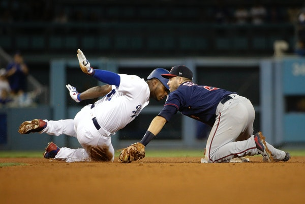 Los Angeles Dodgers' Yasiel Puig, left, is tagged out by Minnesota Twins' Brian Dozier during the sixth inning of a baseball game, Tuesday, July 25, 2