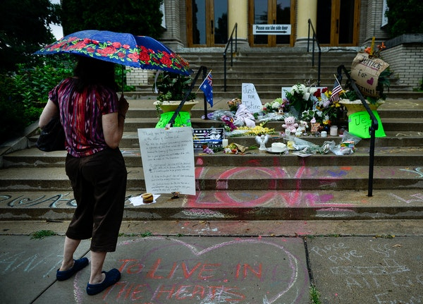 A woman viewed the memorial to Justine Damond on the steps of the Lake Harriet Spiritual Community building in south Minneapolis on Wednesday.