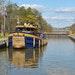 A tugboat in a lock on the Erie Canal, above. Top photos: Lock 35 in Lockport, N.Y., both in 1917 and today.