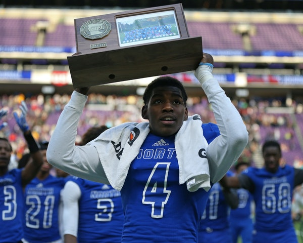 Phaizon Scott brought the Minneapolis North championship trophy to the crowd after the Polars defeated Rushford-Peterson 30-14. ] Shari L. Gross / sgr