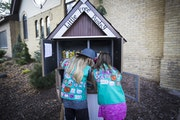 Justine Meyers and Zoey Myers, members of Troop 1554, stocked their Little Free Pantry Tuesday in Chaska.
