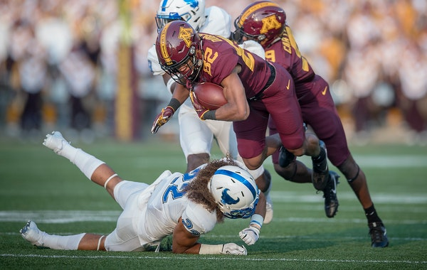 Minnesota's wide receiver Demetrius Douglas rushed for yards before being stopped by Buffalo's safety Tim Roberts during the first quarter the Gophers