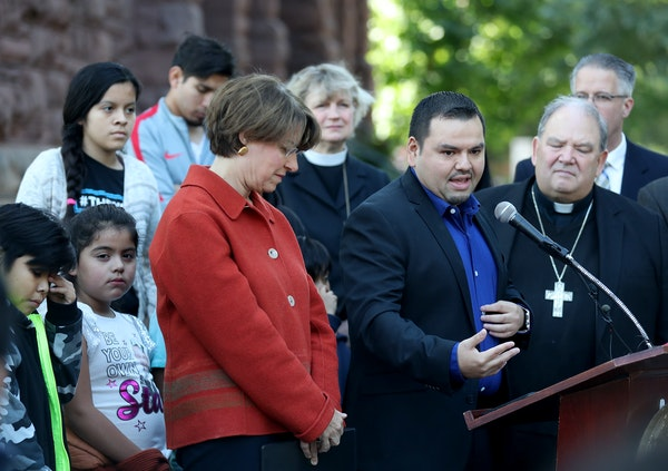 David Soto, 31, a Twin Cities financial adviser, at microphone, flanked by Sen. Amy Klobuchar, left, and Archbishop Bernard Hebda, right, described hi