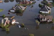 In this aerial photo, homes sit in floodwaters caused Tropical Storm Harvey in Port Arthur, Texas, Friday, Sept. 1, 2017. Port Arthur's major roads we