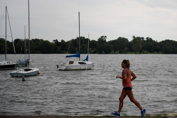 A runner jogs past a boat launch area near the main beach of Lake Nokomis. The higher ozone levels expected Friday can Higher ozone levels can affect