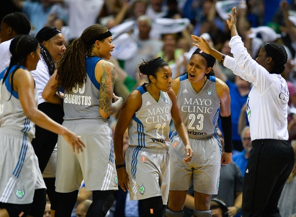 Teammates celebrated around Minnesota Lynx guard Renee Montgomery (21) after her buzzer beater to end the third quarter Tuesday night against the Wash