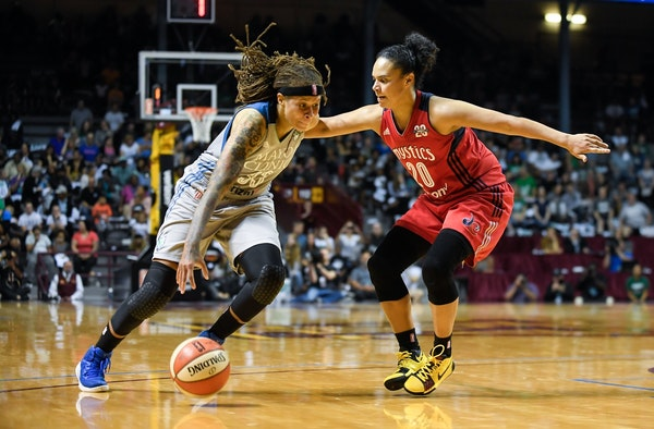 Minnesota Lynx guard Seimone Augustus (33) moved the ball toward the basket while being defended by Washington Mystics guard Kristi Toliver (20) in th