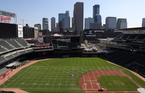 Groundskeepers worked to transform Target Field from a baseball to a football configuration in preparation for Saturday's game between St. Thomas an
