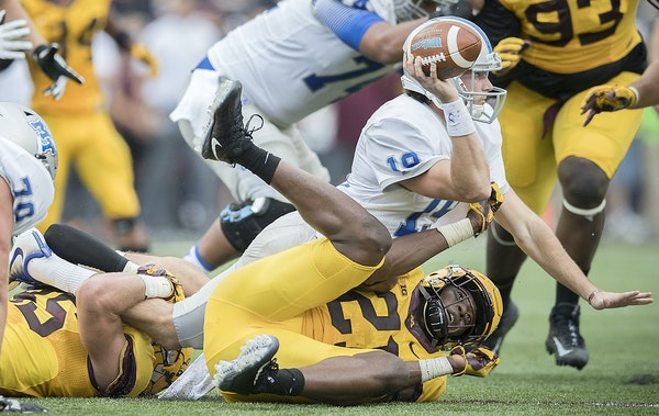 Gophers linebackers Kamal Martin (21) and Carter Coughlin, who grabbed a leg, brought down Middle Tennessee quarterback John Urzua in the second quart