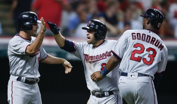 Minnesota Twins' Brian Dozier (2) celebrates with Niko Goodrum (23) and Zack Granite (8) after hitting a three run home run off Cleveland Indians reli