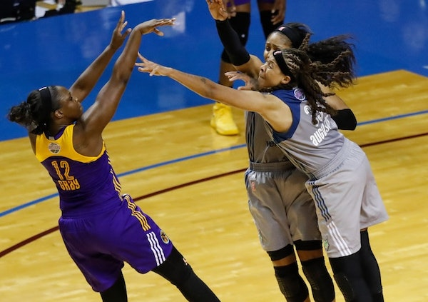 Los Angeles Sparks guard Chelsea Gray (12) shoots the game-winning shot as Minnesota Lynx forward Maya Moore (23) and guard Seimone Augustus (33) appl