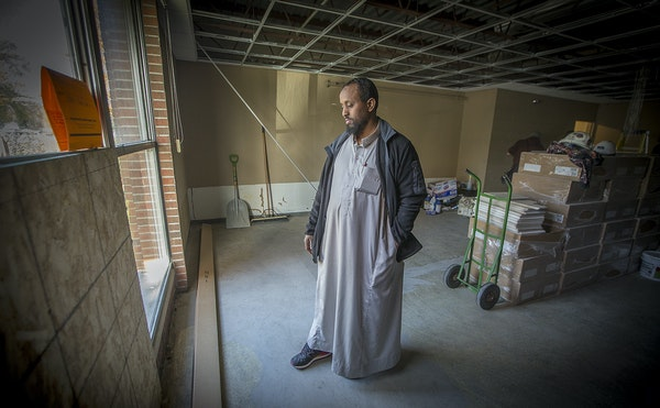 Mohamed Omar looked out the now-repaired window that was shattered from an explosive device at the Dar Al Farooq Center in Bloomington.