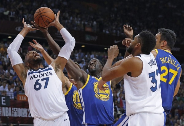 The Timberwolves' Taj Gibson, left, fought for the ball with the Warriors' Draymond Green, center, during the NBA Global Games in Shenzhen, south Chin
