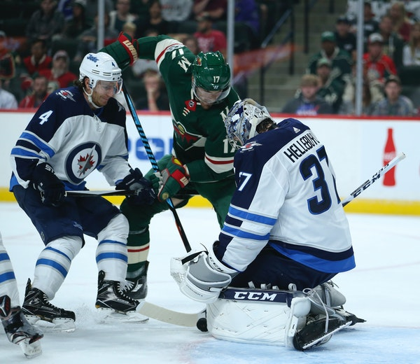 Minnesota Wild left wing Marcus Foligno (17) tries to shove the puck between the pads of Winnipeg Jets goalie Connor Hellebuyck (37) while defended by