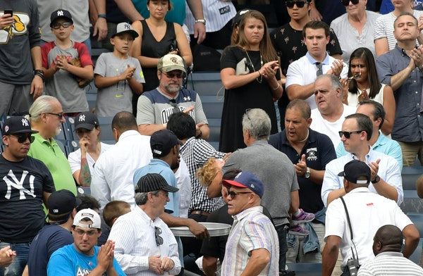 Baseball fans reacts as a young girl is carried out of the seating area after being hit by a line drive during the fifth inning of a baseball game bet