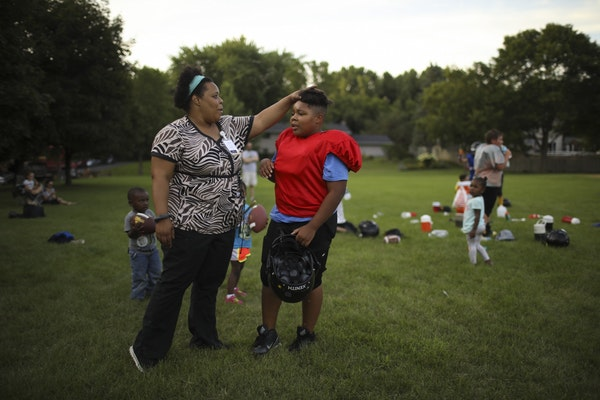 Kathryn Lusack checked in with her son, Roderick Bright, 11, when he took a water break during football practice Tuesday evening at Knob Hill Park in
