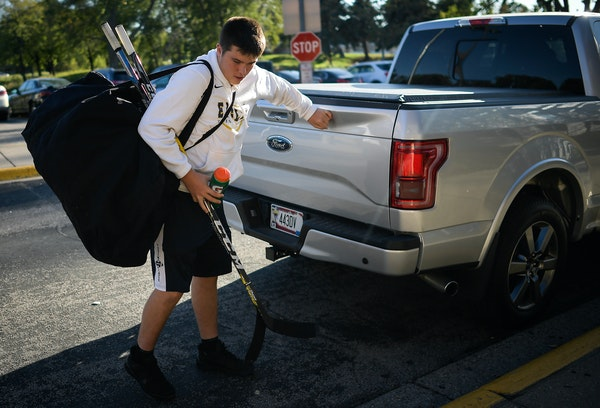 Totino-Grace freshman Luke Rooker grabbed his hockey gear from his father's truck as he walked into the Brooklyn Park Community Center ice arena for p
