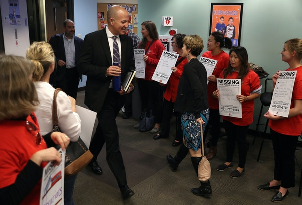 Superintendent Joe Gothard made his way past members of the St. Paul teachers union, wearing their signature red shirts, at a demonstration outside Tu