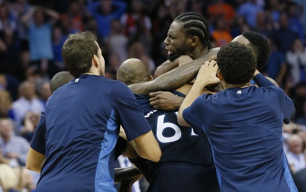 Minnesota Timberwolves guard Andrew Wiggins, center, is mobbed by his teammates after hitting the game winning shot at the buzzer in the fourth quarte