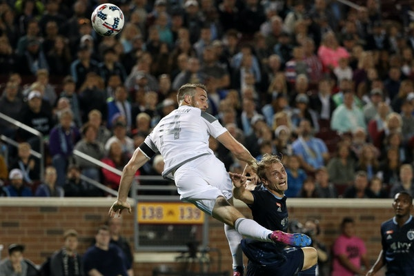 Minnesota United defender Brent Kallman (14) and Sporting Kansas City defender Seth Sinovic (15) rise up for a loose ball in the first half