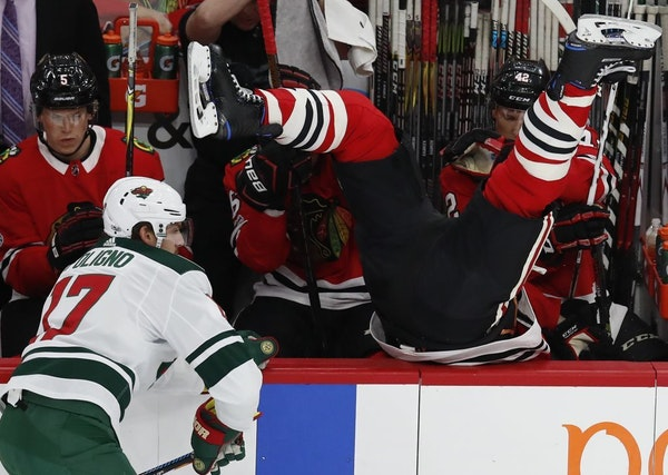 Chicago Blackhawks' Brent Seabrook, right, goes over the boards after missing a check on Minnesota Wild's Marcus Foligno during the first period of an