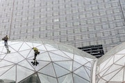 Window washers work on a recently built trio of geodesic domes that are part of Amazon's headquarters building, visible in the background, in Seattle,