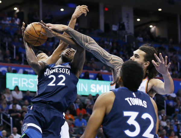 Minnesota Timberwolves guard Andrew Wiggins (22) is fouled by Oklahoma City Thunder center Steven Adams, right, as he shoots between Adams and Andre R