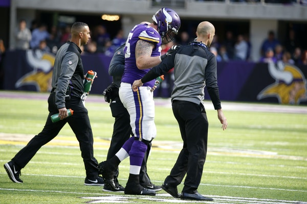 Minnesota Vikings guard Jeremiah Sirles (75) is helped off the field after getting injured during the first half of an NFL football game against the B