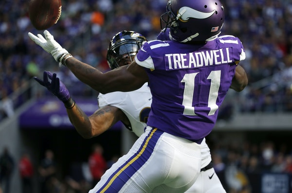 Baltimore Ravens cornerback Brandon Carr, rear, intercepts a pass intended for Minnesota Vikings wide receiver Laquon Treadwell (11) during the first
