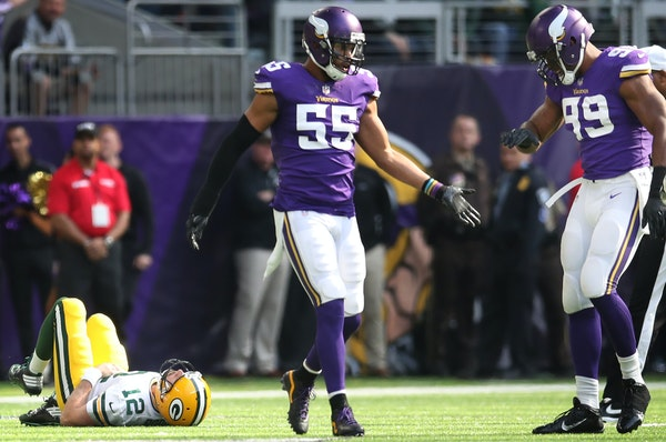 The Vikings' Anthony Barr (55, with Danielle Hunter) hit Packers QB Aaron Rodgers just after he threw a first-quarter pass. The news got worse for G