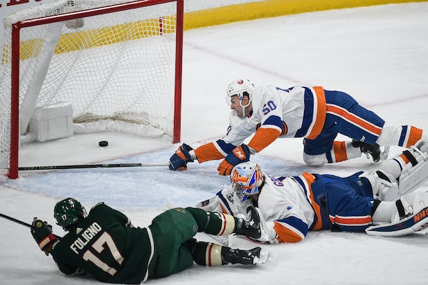 New York Islanders defenseman Adam Pelech (50) was unable to stop the puck as Minnesota Wild left wing Marcus Foligno (17) scored a goal on New York I