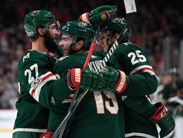The Minnesota Wild's Kyle Quincey (27) and Jonas Brodin (25) celebrate with Luke Kunin (19) after Kunin scored the first NHL goal of his career in the