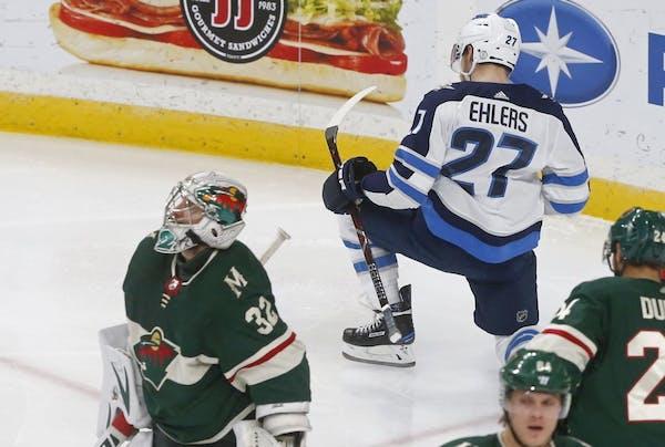 Winnipeg Jets' Nikolaj Ehlers, right, of Denmark, celebrates as he scores on Minnesota Wild goalie Alex Stalock, left, during the third period of an N