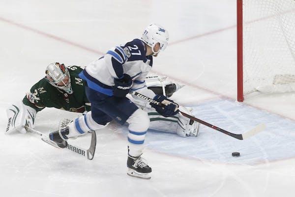 Winnipeg Jets' Nikolaj Ehlers, right, of Denmark, skates past Minnesota Wild goalie Alex Stalock to score during the third period of an NHL hockey gam