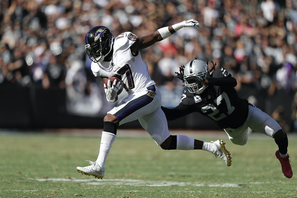 Baltimore Ravens wide receiver Mike Wallace (17) runs past Oakland Raiders free safety Reggie Nelson (27) during the second half of an NFL football ga