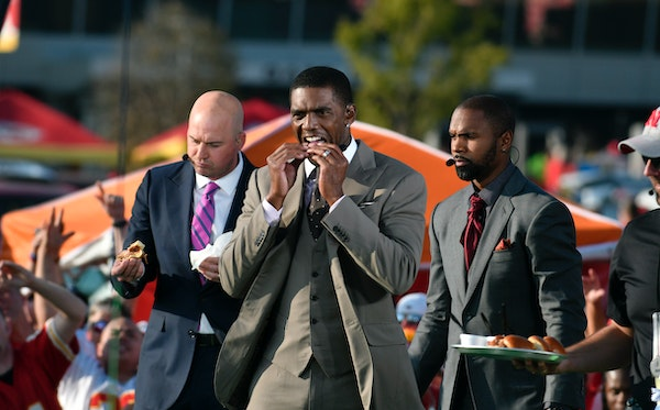 ESPN hosts from left: Matt Hasselbeck, Randy Moss and Charles Woodson sample food during a tailgating special outside Arrowhead Stadium before an NFL