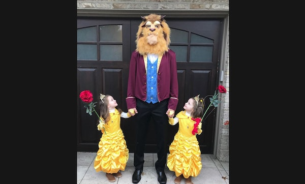 Joe Mauer and his twin daughters Emily and Maren as Beauties and the Beast for Halloween.