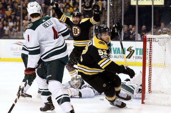 Boston Bruins' Sean Kuraly celebrates his goal on Minnesota Wild goalie Devan Dubnyk as defenseman Mike Reilly (4) looks on during the second period o