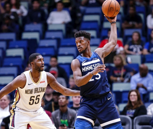 Minnesota Timberwolves guard Jimmy Butler (23) works against New Orleans Pelicans guard E'Twaun Moore (55) in the first half of an NBA basketball game