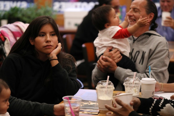 Missy Jackson, left, listened Thursday in Minneapolis during a Natives Against Heroin meeting as group founder James Cross held her 9-month-old daught