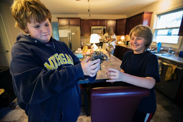 Brothers Eian, 13, and Owen, 10, Farchmin played with their new turtle. Their mother recently died from a drug overdose.