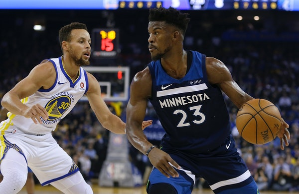 Minnesota Timberwolves' Jimmy Butler, right, drives the ball against Golden State Warriors' Stephen Curry (30) during the first half of an NBA basketb