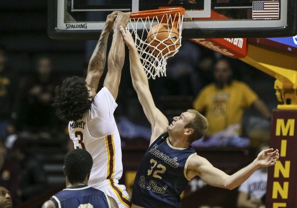 Minnesota's Jordan Murphy (3) dunked the ball during the first half as Concordia's Max Keefe (32) tried to stop him.