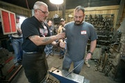 """Ken Zitur, left, gave a lesson to veterans including Aaron Othoudt. Why did he and a buddy show up? """"We were both interested in pounding on metal.�"""