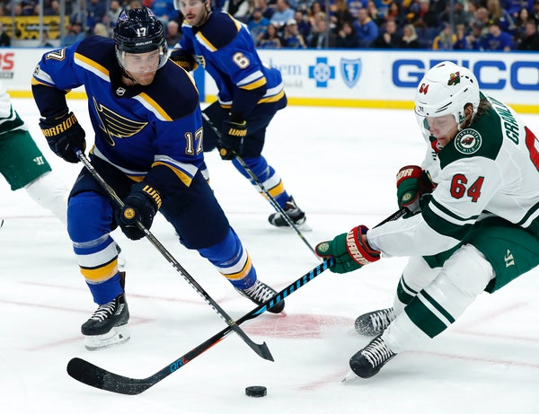 St. Louis Blues' Jaden Schwartz (17) and Minnesota Wild's Mikael Granlund chase after a loose puck